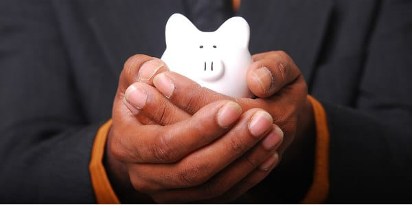 man holding piggybank to save money